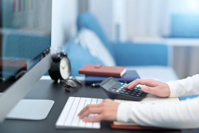 Young business woman work with calculator and computer desktop